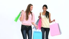 Friends kissing while holding shopping bags. Against white background stock video footage