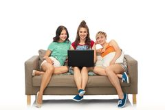 Friends with laptop computer sitting on sofa stock images