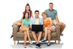 Friends with laptop computer sitting on sofa stock photography