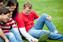 Friends with laptop outdoors Stock Photography