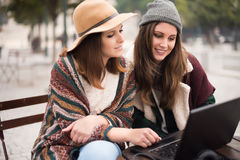 Friends in laptop on street Stock Photography