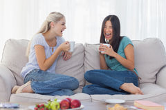 Friends laughing and drinking coffee together Stock Photo