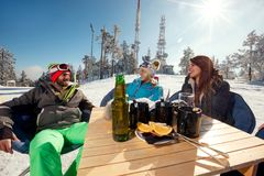 Friends laughing and enjoying in drink at ski resort. Together Royalty Free Stock Photography