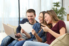 Friends laughing hard watching videos at home. Three happy friends laughing hard watching videos sitting on a couch at home Royalty Free Stock Photo