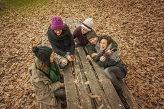 Friends laughing sit in a wood bench of the park. Stock Images