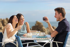 Friends laughing and taking photo with a smart phone. Friends on vacations laughing and taking photo with a smart phone in a restaurant on the beach Stock Photo