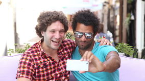 Friends laughing and taking a selfie. Two young men having fun while taking selfies in town stock footage