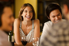 Friends laughing together. In a restaurant at night Stock Photo