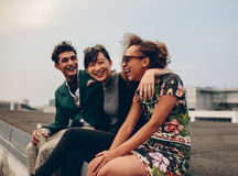Friends laughing together on rooftop. Shot of happy young friends relaxing together on rooftop. Young men and women sitting on terrace and laughing Royalty Free Stock Images
