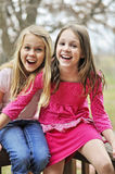 Friends laughing. Two girls looking in shocked disbelief at the camera  and laughing Stock Photography
