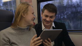 Friends laughing while using pad in train stock video footage