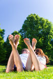 Friends laying in park Stock Photo