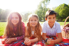 Friends laying on the picnic blanket at sunny day. Close-up portrait of three happy friends laying on the picnic blanket in a line next to the basket at sunny Royalty Free Stock Images
