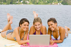 Friends laying on pier with laptop Stock Photo