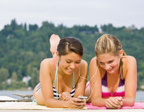 Friends laying on pier listening to mp3 player Royalty Free Stock Images