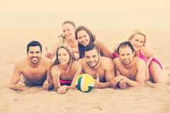 Friends laying on sand at beach. Positive young adults relaxing at sandy beach in sunny day. Selective focus Royalty Free Stock Image