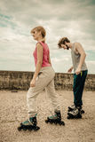 Friends learn rollerblading together have fun at park. Royalty Free Stock Photo