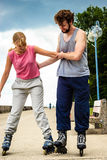 Friends learn rollerblading together have fun at park. Stock Photos
