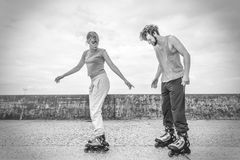 Friends learn rollerblading together have fun at park. Royalty Free Stock Images