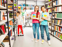 Friends in the library stand together with  books Stock Photo
