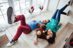 Friends lie alongside opposite heads on wooden floor. royalty free stock photography
