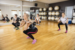 Friends Lifting Barbells In Fitness Club Stock Photo