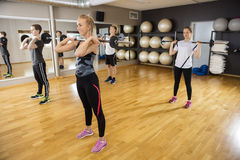 Friends Lifting Barbells While Standing In Fitness Club Stock Photography