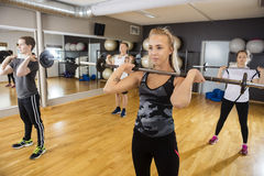Friends Lifting Barbells While Standing In Health Club Royalty Free Stock Photography