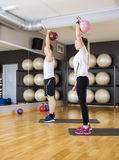 Friends Lifting Kettlebells While Standing On Mat In Gym Royalty Free Stock Image
