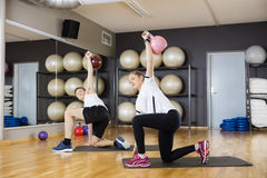 Friends Lifting Kettlebells in Turkish Getup Royalty Free Stock Images