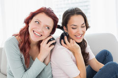 Friends listening music through headphones together at home Royalty Free Stock Image