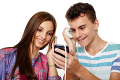 Friends listening music together. From a cellphone on the same pair of headphones Stock Photography