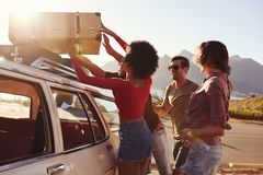 Friends Loading Luggage Onto Car Roof Rack Ready For Road Trip Royalty Free Stock Photography