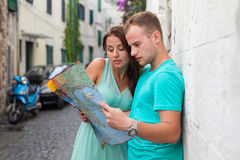 Friends loking on the map on the street. They are on holidays. Royalty Free Stock Image