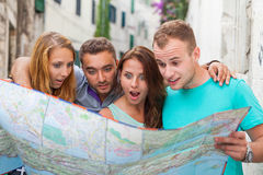 Friends loking on the map on the street. They are on holidays. Royalty Free Stock Images