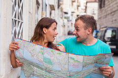 Friends loking on the map on the street. They are on holidays. Stock Images