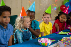 Friends looking at boy whispering to girl. While sitting at table during birthday party Royalty Free Stock Photos