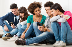 Friends Looking At Cell Phone. Group Of Happy Young Friends Looking At Cell Phone Royalty Free Stock Image