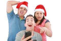 Friends looking at cellphone with Christmas hat Royalty Free Stock Photography