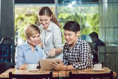 Friends looking at digital tablet sitting in the coffee shop royalty free stock image