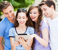 Friends looking at digital tablet. 