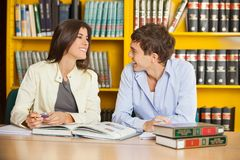Friends Looking At Each Other Against Bookshelf In. Happy college friends looking at each other while sitting against bookshelf in library Stock Image