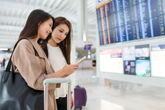 Friends looking for flight number in airport Stock Photo