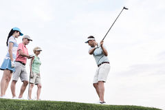 Friends looking at man playing golf against sky Royalty Free Stock Photos