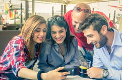 Friends looking at mobile phone in a bar Stock Photography