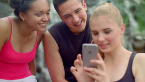 Friends looking at phone. Young friends smiling. Blonde woman smartphone stock video