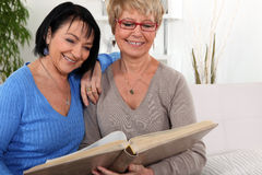 Friends looking at a photo album royalty free stock photography