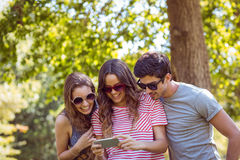 Friends looking photos in a park Stock Photo