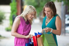 Friends Looking Into Shopping Bags Stock Images