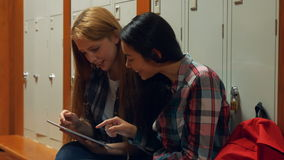 Friends looking at a tablet pc together. In the university college stock footage